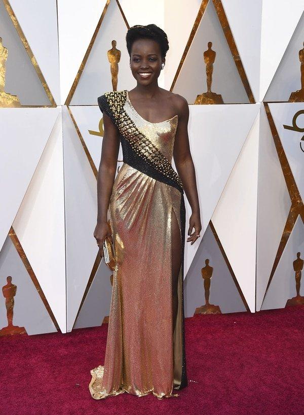 """Lupita Nyong'o se arriesgó al metalizado y negro. Con corte asimétrico y un tajo en la falda, deslumbró en la red carpet. La diseñadora Maureene Dinar opinó """"Definitivamente da muy bien en foto pero viéndola no me gusta para nada"""""""