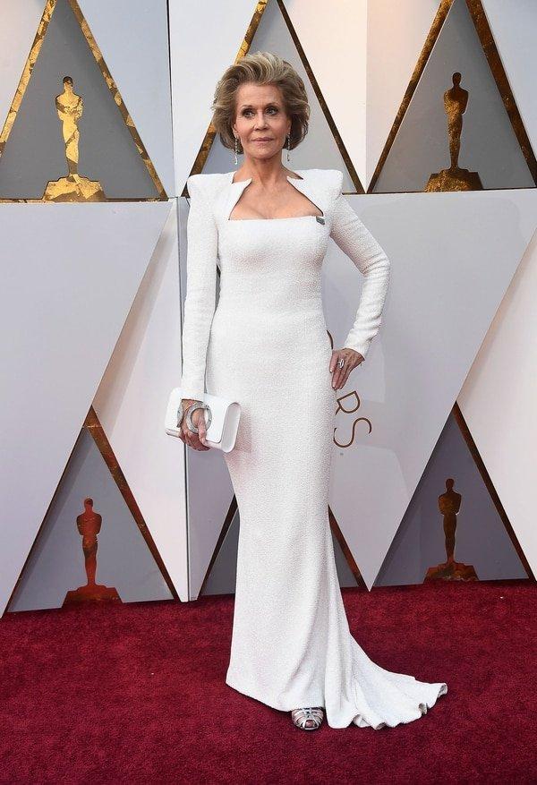 """Jane Fonda enfundada en un total white look by Balmain. """"La primera en impactar"""", dijo Caprarola. Con mangas y hombros estructurados, el diseño sirena bordado fue uno de los más halagados de la red carpet. Los complementos elegidos por Fonda en plateados. Sandalias, clutch combinado y delicadas joyas"""