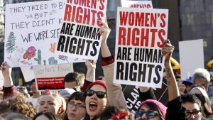 Women chant and raise their signs during a rally, part of International Women's Strike NYC, a coalition of dozens of grassroots groups and labor organizations, Wednesday, March 8, 2017, at Washington Square Park in New York. (AP Photo/Kathy Willens)