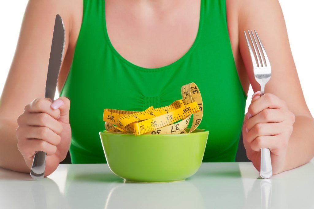 Concept image of a woman on a diet, eating a measuring tape, isolated on white