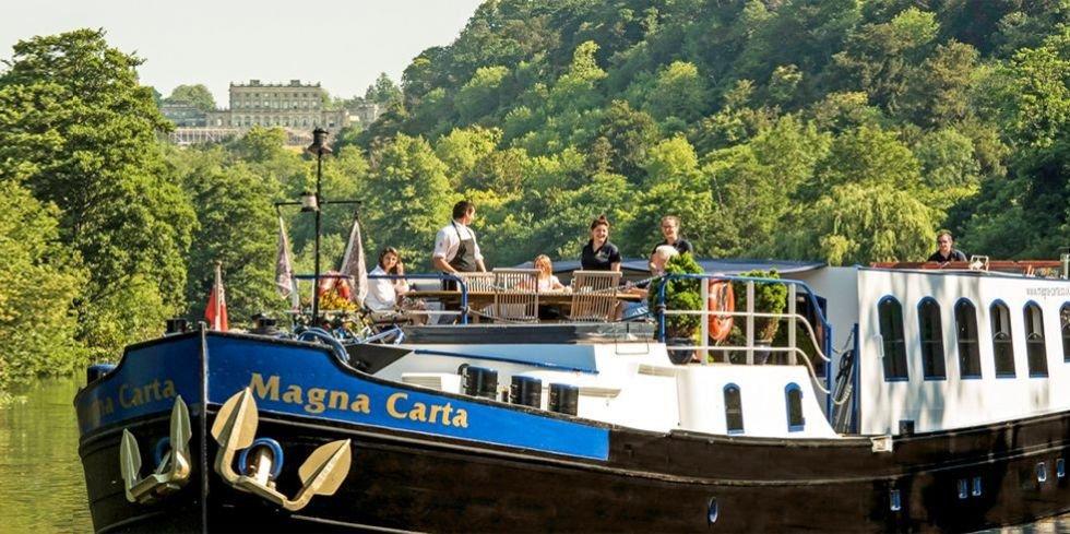 Barco Magna Carta com pessoas na parte da frente em cima de uma mesa