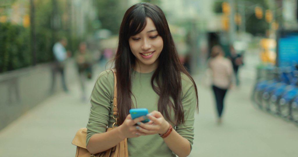 young-asian-woman-walking-texting-smart-phone-cellphone-in-city-4k_nkitrvhx__f0000