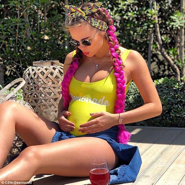 Xenia Deli, 28, está esperando seu primeiro filho com seu marido bilionário, postando esse estalo de sua barriga protuberante sob um top amarelo e segurando seu estômago para o Instagram