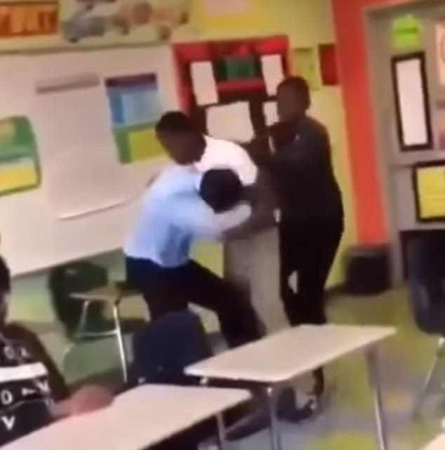 The student arose from the ground to attack the teacher once again as his peer tried to pull him back