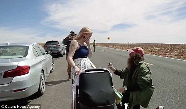 Nadine holds their newborn baby Bee in a pram as Rob gets down on one knee to ask