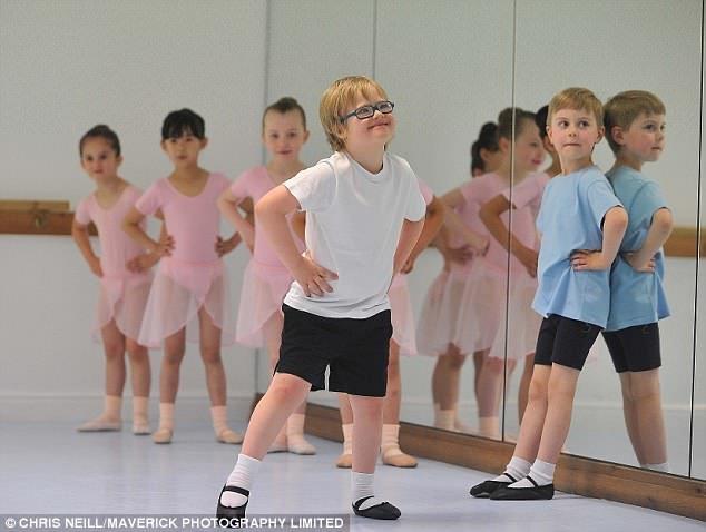 Sourire effronté: l'écolier pose les mains sur les hanches alors qu'il sourit à Mme O