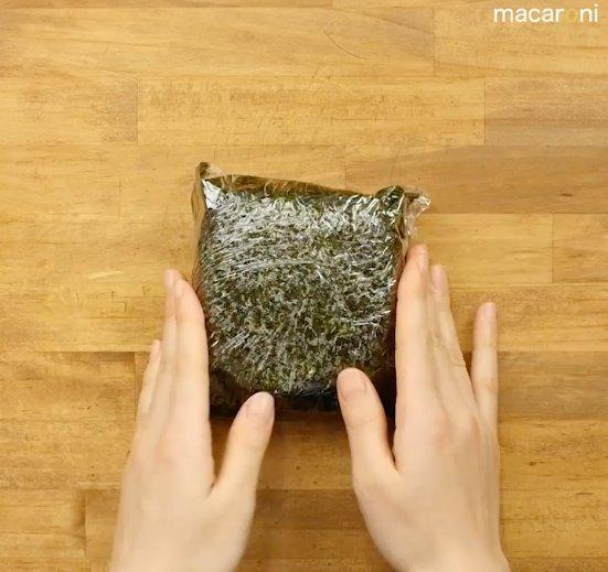 ラップで海苔とご飯を包んでいる画像