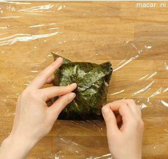 海苔で具材とご飯を包んでいる画像
