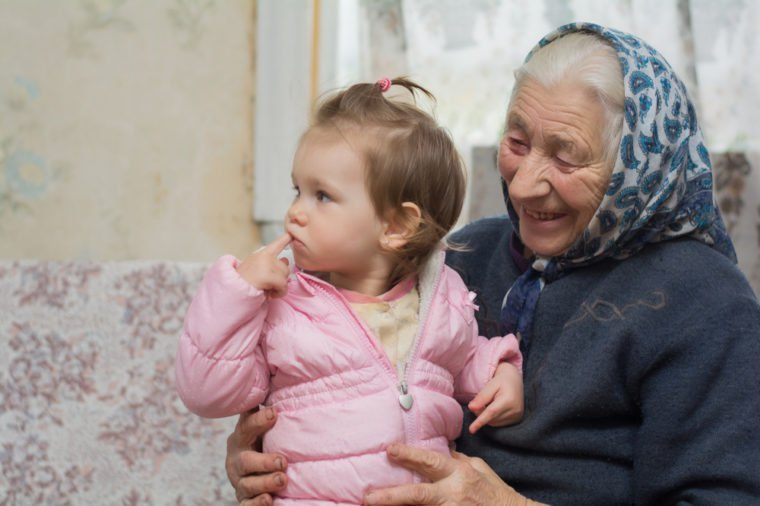 An elderly grandmother holds a small beautiful baby on her wrinkled arms. family generation. Youth and old age