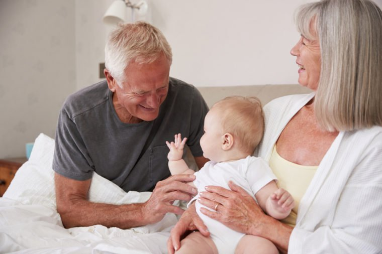 Grandparents Lying In Bed At Home Looking After Baby Grandson