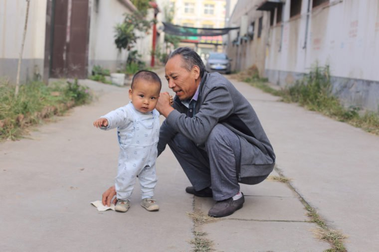 1 year old cute baby boy learning walk with grandpa, most old people in China are in charging of taking care of their grandchildren