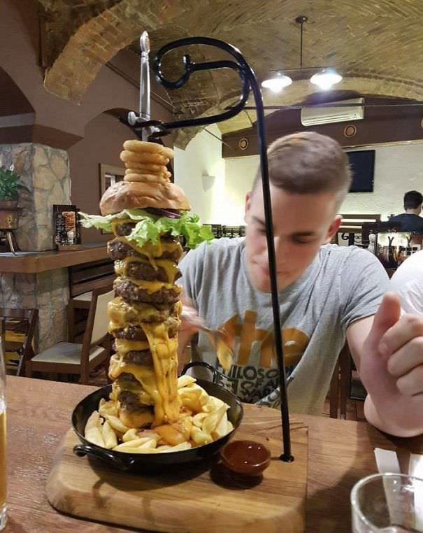 Terrible Bun: Meat Ratio And Precariously Tall Burger On A Skillet On A Board With A Sword Through It