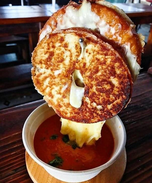 Grilled Cheese Suspended On Metal Hook Above Bowl Of Soup