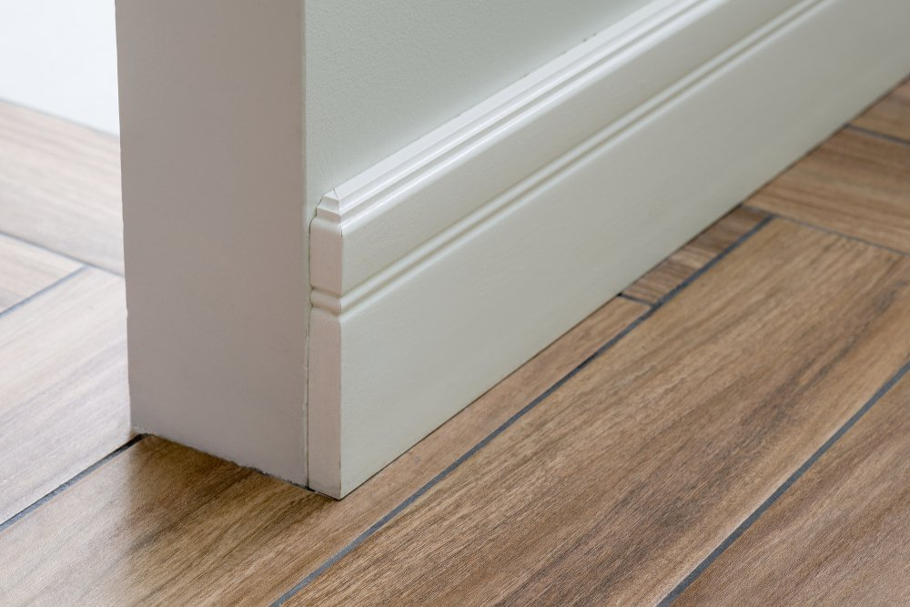 Moulding in the corner. Light matte wall with tiles immitating hardwood flooring