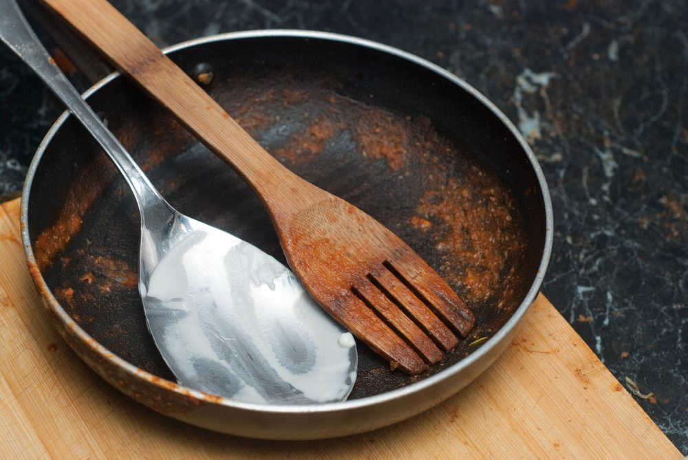 Dirty Pan with Tomato Sauce and Spoons. Dirty Dishes from the Cooking Process.