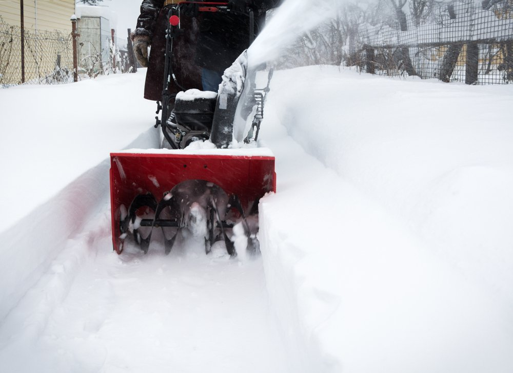 Man clears snow with snow blower after snowfall
