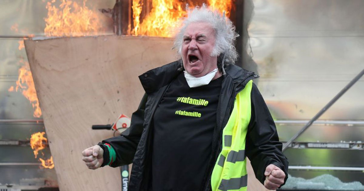 yellow vest protester attempts to throw back a tear gas canister during clashes with riot police.jpg?resize=412,232 - Yellow Vest Protesters Smash And Set Fire On Stores In Paris