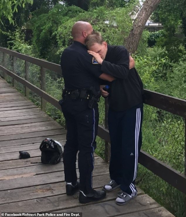 Lance Grumley, 31, hugs police officer Thompson after he was safely found on Wednesday