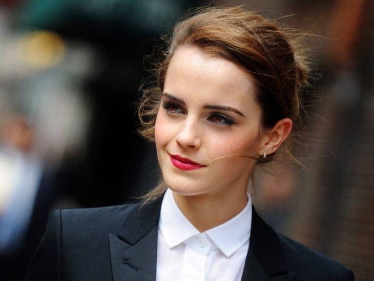 Emma Watson sonriendo ligeramente y llevando traje sastre