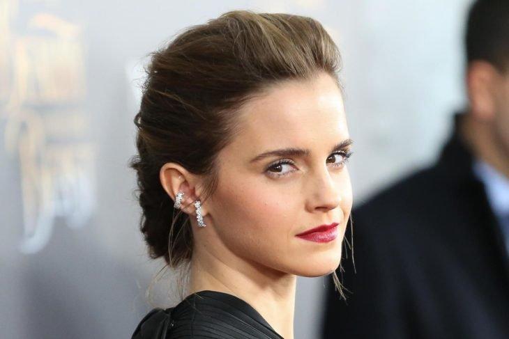 Emma Watson posando de perfil para una fotografía durante una alfombra roja