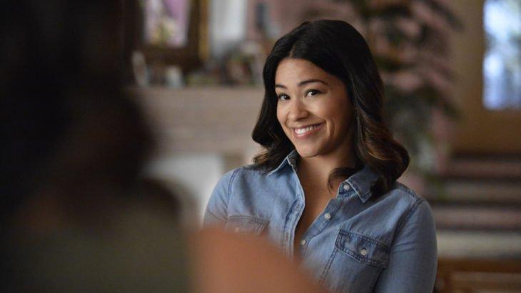 Jane Villanueva sonriendo y charlo con una persona, escena de la serie Jane the Virgin