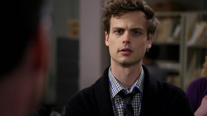 Spencer Reid sorprendido dentro de una oficina charlando con otra persona, escena de la serie Mentes Criminales