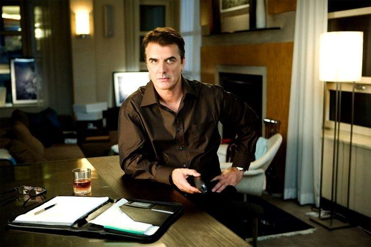 El actor Chris Noth sentado en un escritorio en la película Sex and the City