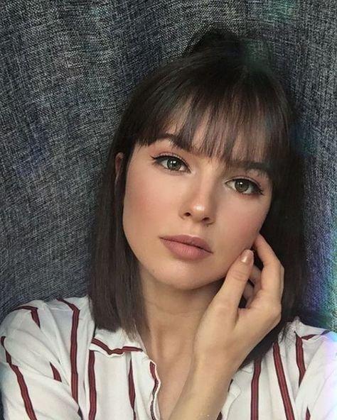Chica con cabello corto recargada en una pared modelando