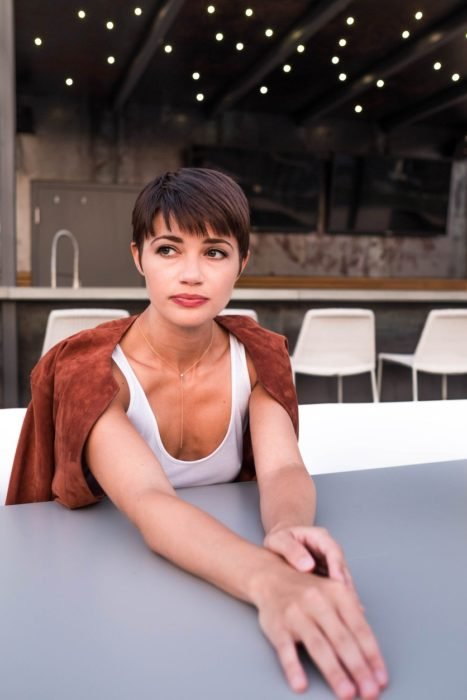 Chica con un corte pixi sentada en un restaurante posando para una fotografía