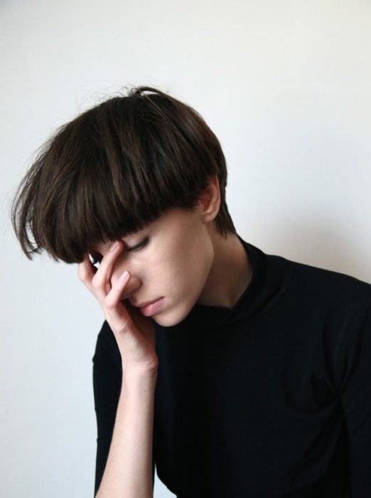 Chica recargando su rostro en su mano, con los ojos cerrados y la cabeza inclinada hacia abajo