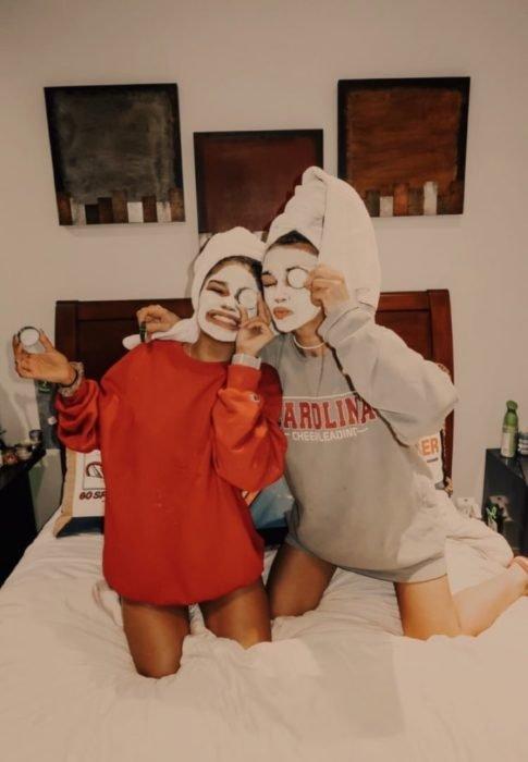amigas sobre una cama usando mascarillas y rodajas de pepino en sesión de spa en casa