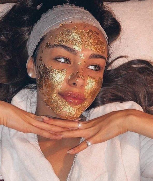 Chica recostada en su cama usando mascarilla dorada