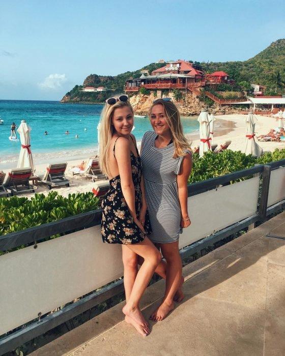 Madre e hija rubias posando descalzas en el malecón frente a la playa, ambas con vestidos playeros y lentes de sol