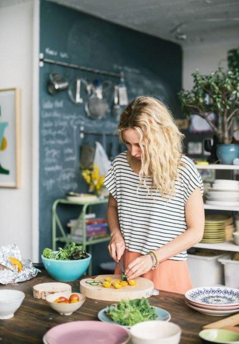 Mujer de cabello rubio y ondulado con blusa a rayas preparando de comer