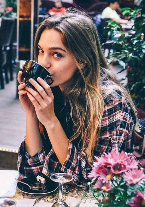 Mujer de cabello rubio y camisa a cuadros bebe una taza de café en un restaurante