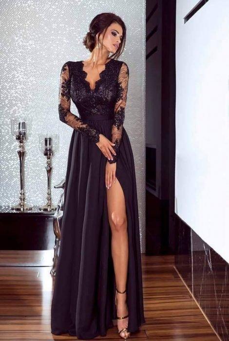 Chica modelando un vestido negro con abertura en la pierna y detalles de encaje en los brazos