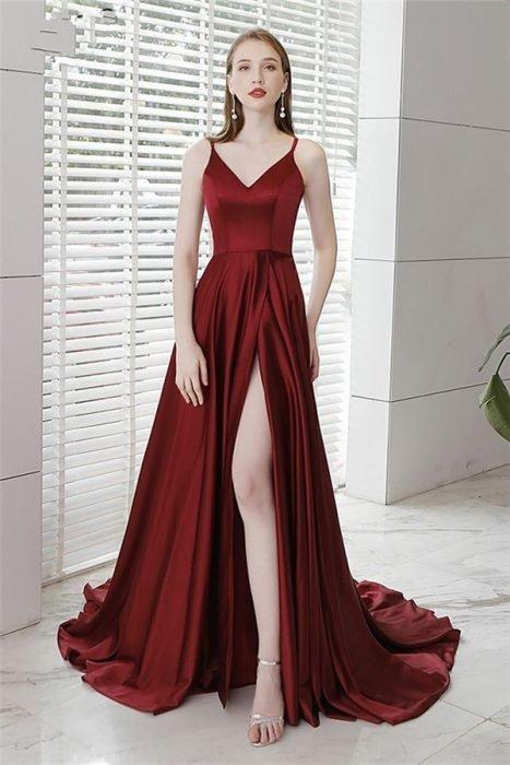Chica frente a una ventana modelando un vestido de color vino con abertura en pierna