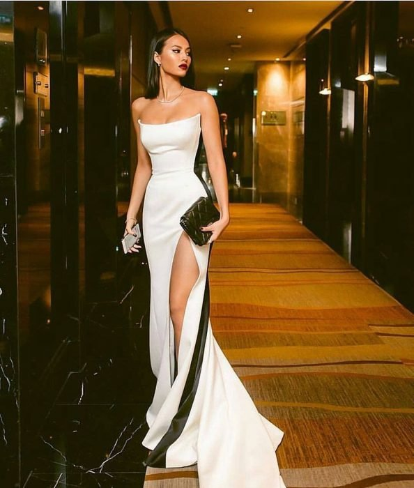 Chica en pasillo modelando un vestido al cuerpo color blanco con detalles laterales en negro