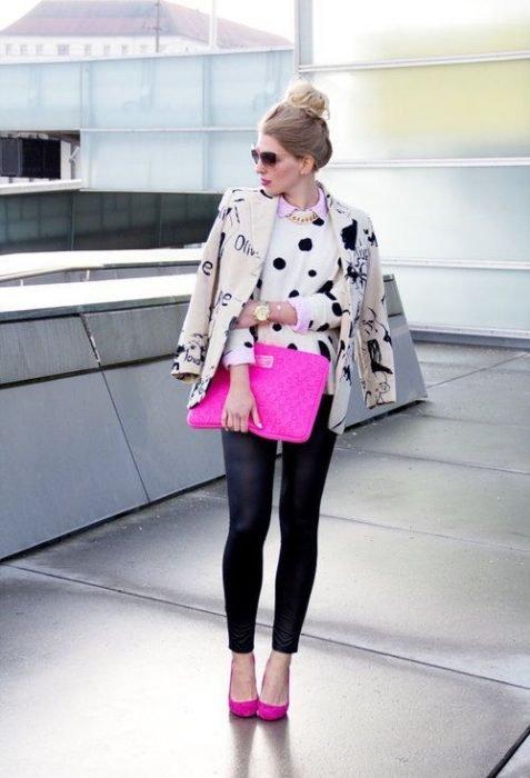 Chica modelando un suéter de lunares, una chamarra de piel, leggins negros y un bolso rosa