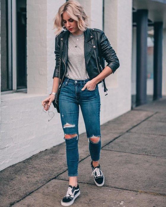 Chica caminando por la calle con jeans de mezclilla rotos, camisa gris, tenis negros con adornos en blancos y una chamarra de cuero