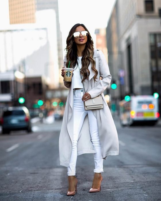 Chica caminando por la calle con atuendo en color blanco, con jeans y saco