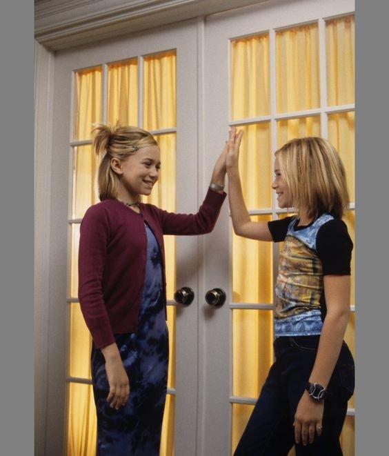 Hermanas Olsen de niñas chocando las palmas afuera de un cuarto