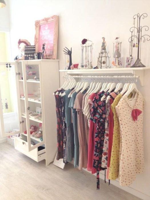 armario elaborado con una repisa de madera y un tubo bajo fijando a la pared con vestidos colgando