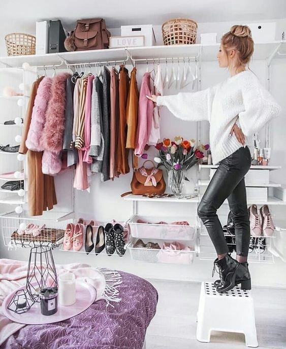 Chica sobre un banco, viendo su armario repleto de ropa