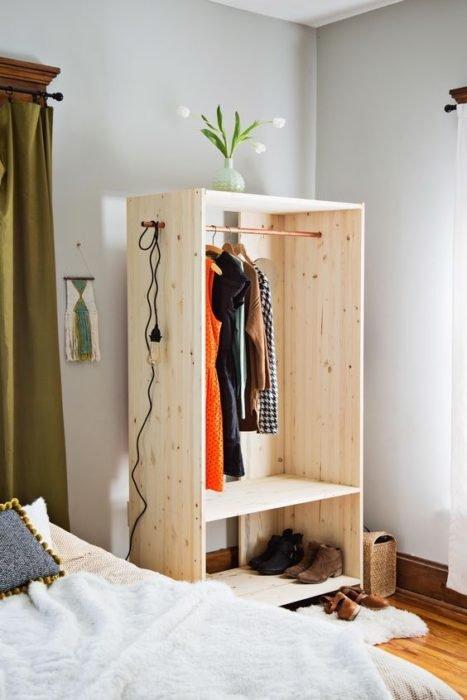 Armario de madera sin puertas junto a una cama, dentro de una habitación blanca