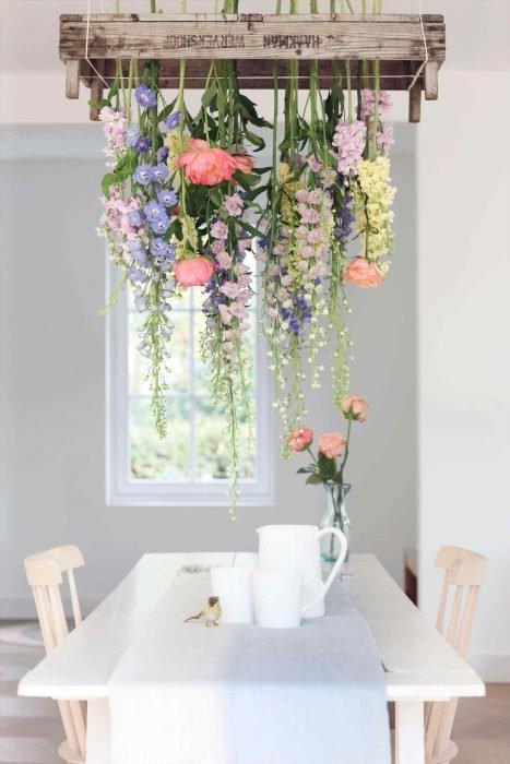 Comedor de una casa en colores neutros, decorada con una cascada de flores que cuelgan desde el techo hasta la mesa