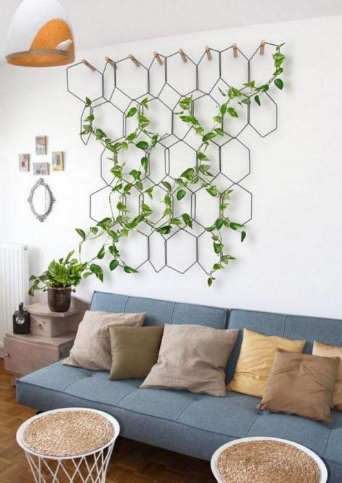 Decoración de sala de estar con una planta trepadora instalada en una estructura metalica de rombos sobre un sillón de color azul con cojines café