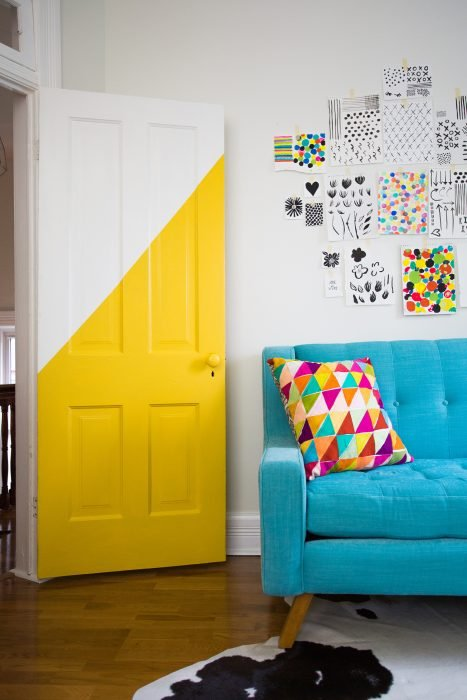 Puerta de una habitación que está aun lado de un sofá azul decorada a la mitad con pintura de color amarillo