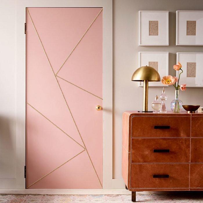 Puerta de una habitación que está junto a una vitrina y unos cuadros pintada de color rosa y decorada con líneas de color dorado