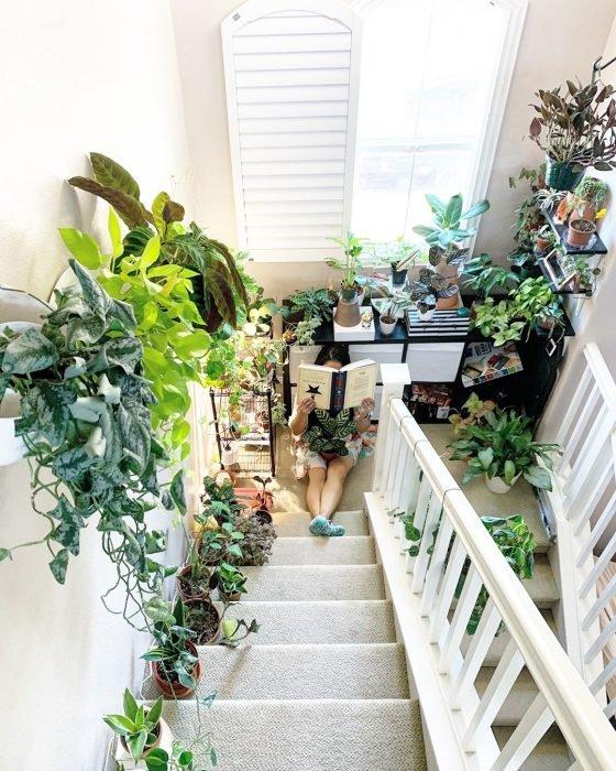 Chica sentada leyendo un libro al final de la escalera. Plantas que rodean los escalones